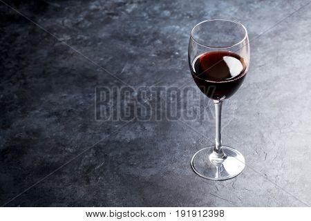 Red wine glass on stone table. With copy space for your text