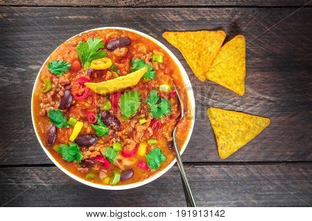 An overhead photo of chili con carne, a traditional Mexican dish with red beans, cilantro leaves, ground meat, and chili peppers, on a dark rustic texture with nachos and a place for text