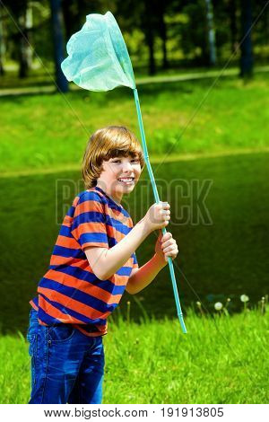 Cheerful boy with a butterfly net runs around the lawn on a sunny summer day.