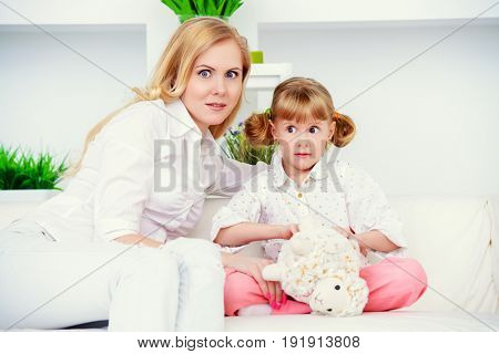 Mom and daughter are sitting with a frightened look.