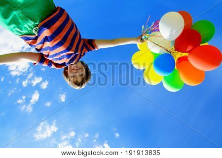 Portrait of a happy boy with many colorful balloons over blue sky. Summer holidays. Birthday.