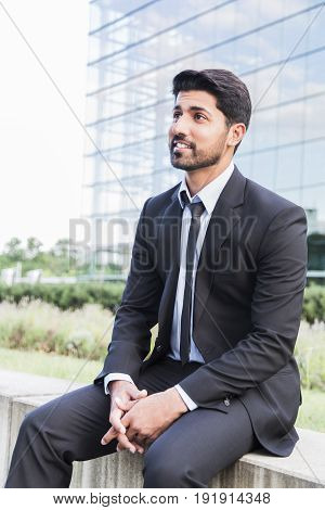 Arabic serious smiling happy successful positive businessman or worker in black suit, white shirt and tie with beard sitting in front of an office glass building.