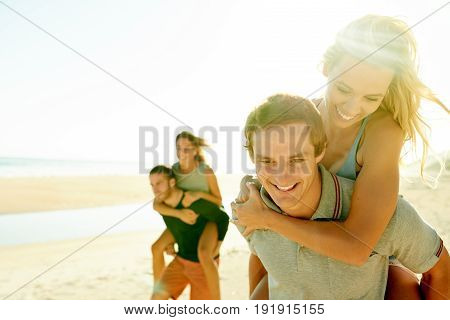Two smiling young couples having a piggyback race together while enjoying a carefree sunny summer's day at the beach