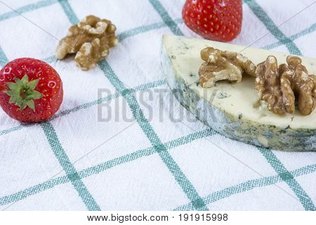One piece of blue cheese roquefort with walnuts and strawberries on the towel