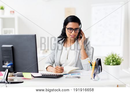 communication, business, people and technology concept - smiling businesswoman or helpline operator with headset and computer talking and writing to notebook at office