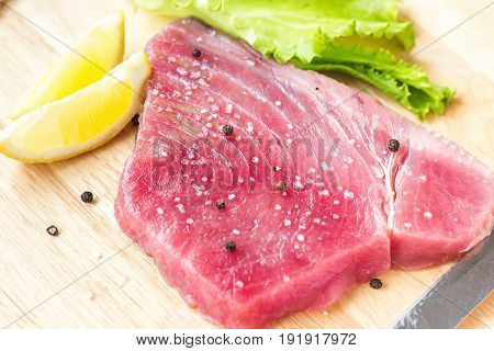 Fresh raw tuna fillet with black pepper corns, salt, lemon and olive oil on rustic background. Raw tuna steak on wooden cutboard, close up, selective focus, ingredients for cooking