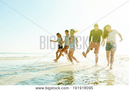 Smiling Friends Splashing Through Water Together At The Beach