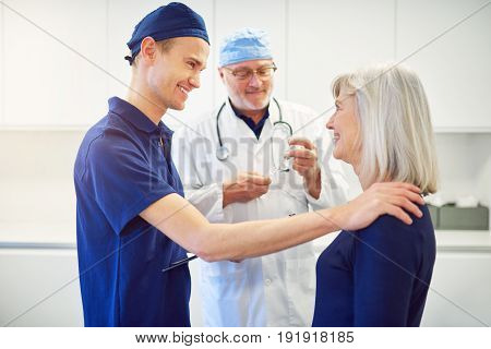 Smiling young medic touching shoulder of adult woman and encouraging her in hospital.