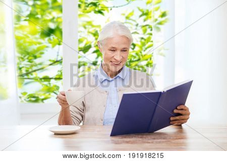 age, leisure and people concept - happy smiling senior woman drinking coffee and reading book at home over window and green natural background