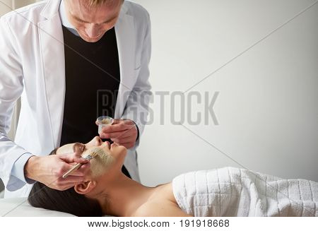 Young Cosmetologist Putting Mask On Female Face With Brush