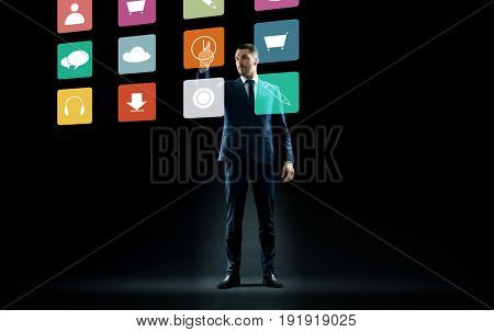 business, people and technology concept - businessman in suit touching virtual menu icons over black background