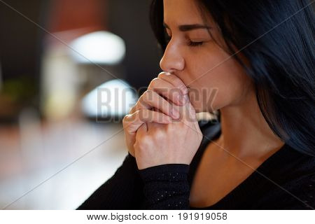 burial, people and mourning concept - close up of unhappy woman praying god at funeral