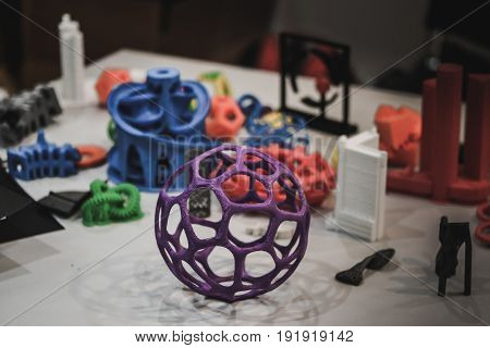 Models printed by 3d printer. Dark. Copy space. Bright colorful objects printed on a 3d printer on a table. Modern additive technologies 4.0 industrial revolution