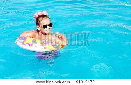 Cute smiling little girl in swimming pool