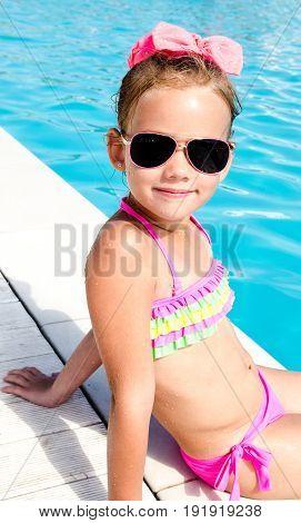 Cute smiling little girl sitting near swimming pool