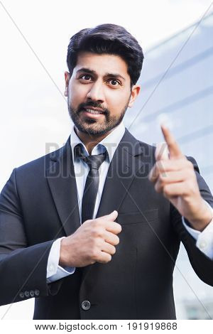 Arabic serious angry irritated aggressive businessman or worker in black suit with beard standing in front of an office glass building with raised hand and pointing his finger at someone.