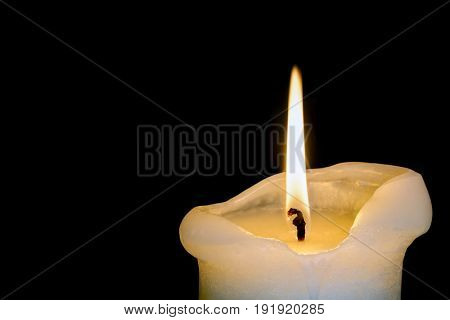 Large candle burning down over black background.
