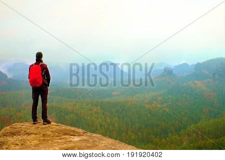 Hiker With Red Backpack On Sharp Sandstone Rock In Rock Empires Park And Watching Over Misty And Fog