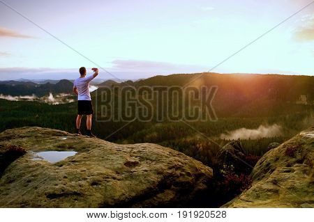 Runner Man In His Target With Hand In The Air. Sweaty Man In Black Pants And White Sweaty T-shirt,