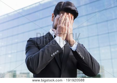 Anonymous disappointed sorry businessman or worker in black suit standing in front of an office glass building with hands on his face.