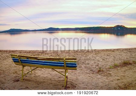Colorful Autumn Evening. Empty Wooden Bench On Beach Of Lake.