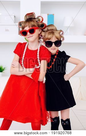 Two funny little girls with curlers in their hair are preparing for a party. Kid's fashion. Family at home.