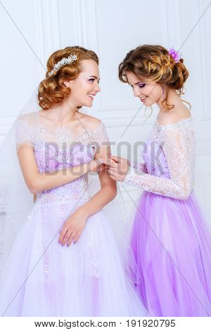 Happy bride girl showing her ring to a bridesmaid. Wedding fashion. Jewellery.