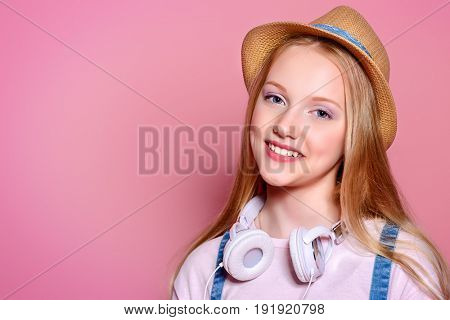 Teen's fashion. Portrait of a cute smiling girl teenager in summer clothes over pink background. Studio shot.