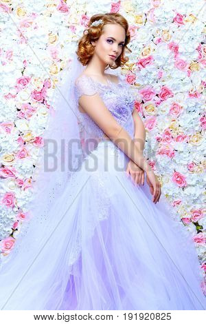 Charming bride in a beautiful dress posing by a background of roses. Wedding fashion.