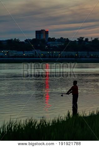 Silhouette of a boy fishing at Angara river after sunset in Irkutsk city
