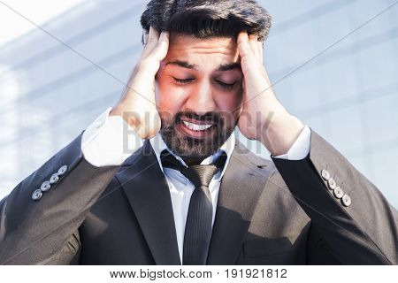 Arabic angry irritated aggressive tired businessman or worker in black suit with beard standing in front of an office glass building with hand on his head. He has a headache.