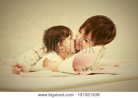 Happy mother and little baby girl reading a book on bed