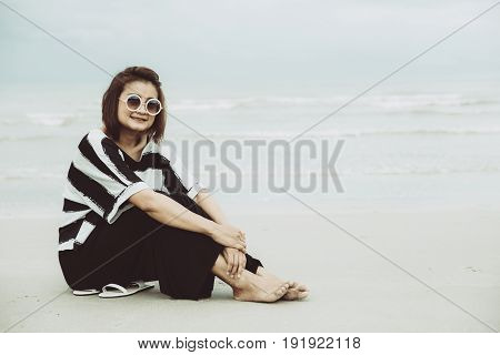 portrait asian single hipster indy women wear sunglasses lonely siting alone on the beach vintage mute color tone.