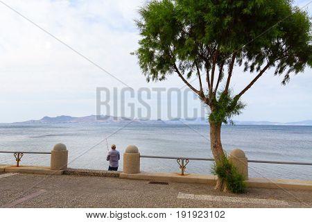 The angler fishing near promenade of Kos town.