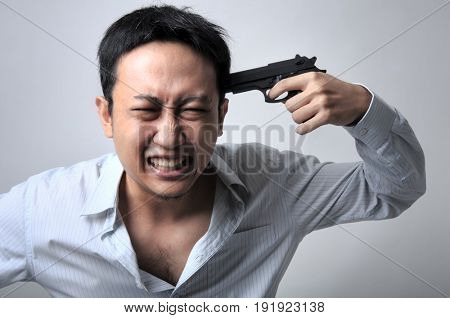 Asian businessman pointing a gun on his head, isolated on grey background.