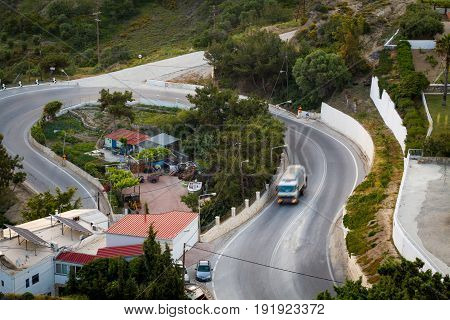 Road curve in the route near Kefalos village with morning work garbage truck. National highway of Greece Island Kos.