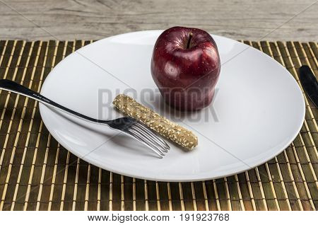 Close up shot of a plate filled only with an apple and a breadstick