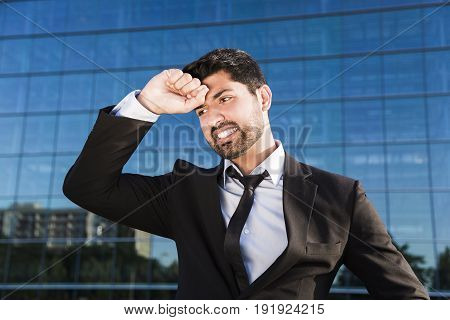 Arabic angry irritated tired businessman or worker in black suit with beard standing in front of an office glass building with hand on his face.