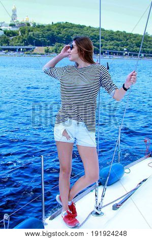 Attractive girl in sailor suit on a yacht at summer day. Adorable woman sailor T-shirt