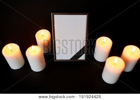 funeral and mourning concept - photo frame with black ribbon and burning candles over dark background