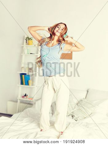 people, leisure and technology concept - happy woman or teenage girl in headphones listening to music and dancing on bed at home