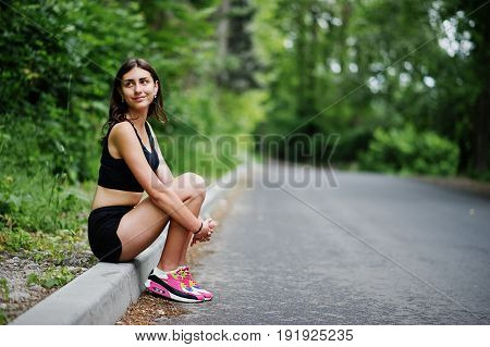 Sport Girl At Sportswear Having Rest In A Green Park After Training At Nature. A Healthy Lifestyle.