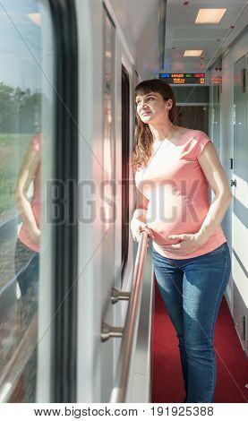 Pregnant European Woman Is Staying And Holding Her Own Tummy Close To Train Window While She Traveli