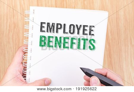 Employee Benefits Word On White Ring Binder Notebook With Hand Holding Pencil On Wood Table,business