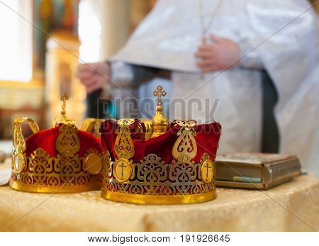 Ceremony Of The Wedding In The Russian Orthodox Church. The Crowns Lie Near The Bible Close Up.