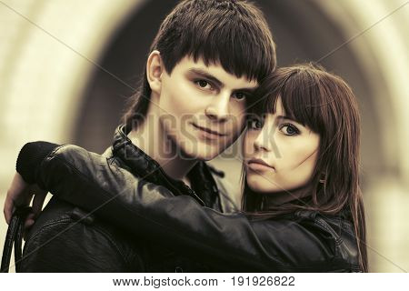 Happy young couple in love embracing in city street. Stylish fashion model in black leather jackets outdoor