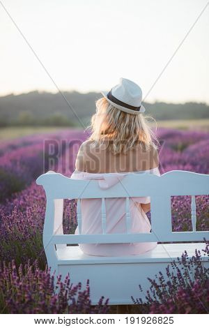 Young woman in straw hat enjoy scenery in lavender field, sitting on a vintage bench.