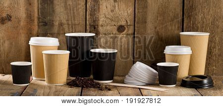 Paper Cups Of Varying Sizes, Coffee Beans, And Wooden Stirrers