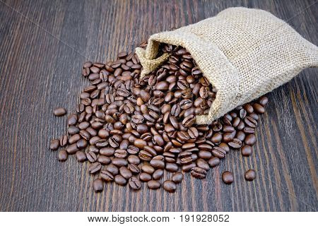 A bag of black coffee beans on a background of a dark wooden board