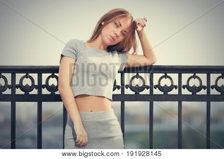 Sad young woman leaning on the cast iron fence. Stylish fashion model in t-shirt outdoor